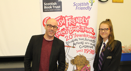 Keith Gray and pupil in front of book tour banner
