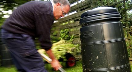 man shovelling compost into compost bin