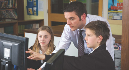 School pupils and teacher looking at computer