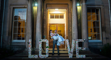 'Love' sign and married couple in front of Normanby Hall