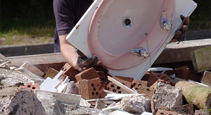 rubble and a used sink in a skip