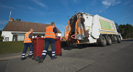 Refuse collectors taking the bins to the wagon to be emptied