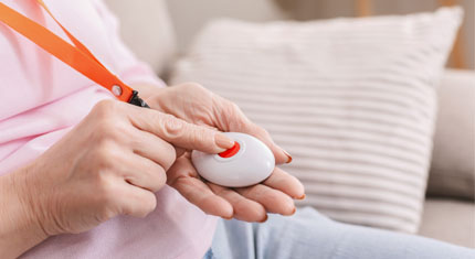 A finger pressing the button on a pendant alarm they are wearing