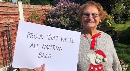 Woman holding a sign with the words ' proud that we are fighting back' which is part of a carer's poem