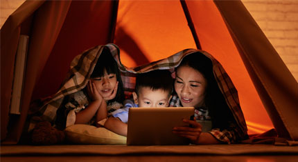 2 children and an adult in a tent reading