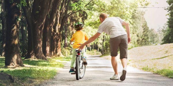 Child learning to ride a bike with adult