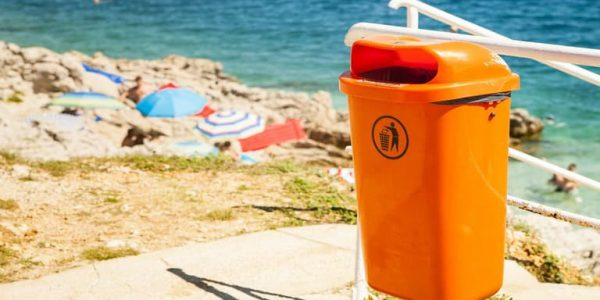 A photograph an orange bin with the sea and people on the beach in the background