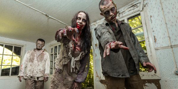Three zombies in an abadoned house lurch towards the camera, arms outstretched