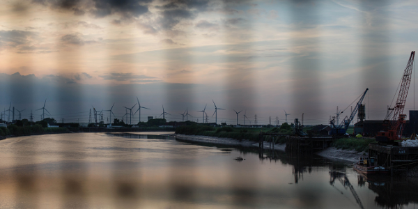 Scenic picture of a stretch of water and clouds with a windfarm in the background