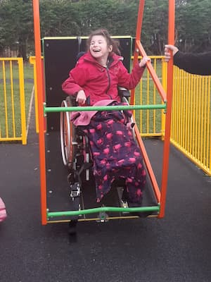 Girl in wheelchair laughing as she uses an access swing in a playpark