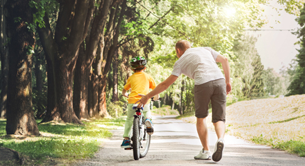Photo of a child riding a bike with an adult's help