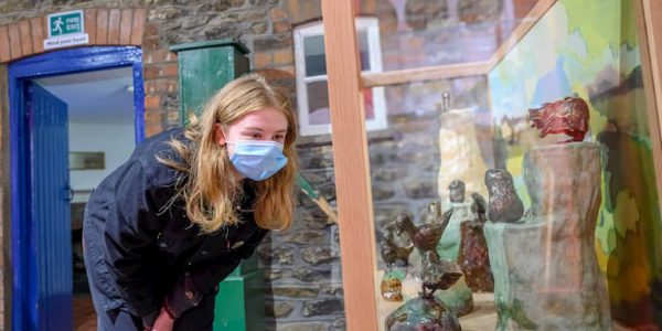Young woman in a face covering looks at a display case of bronze birds at North Lincolnshire Museum