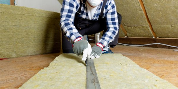 Photograph of man installing thermal roof insulation layer