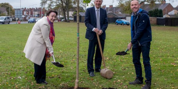 Holly MUmby Croft MP, Cllr David Rose, Cllr Rob Waltham planting a tree on a grassed area in Scunthorpe