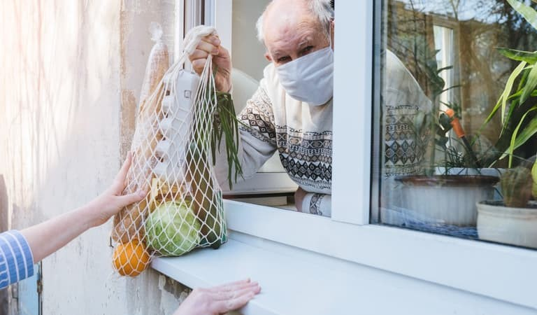 Older man at home self isolating, wearing a mask and receiving shopping through his window
