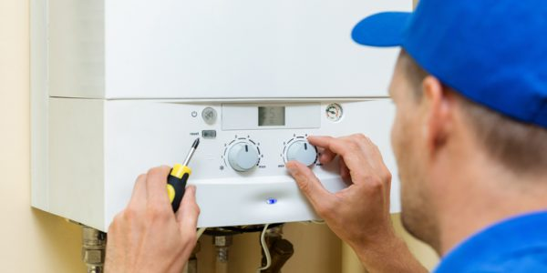 Photograph of a worker setting up a central gas heating boiler