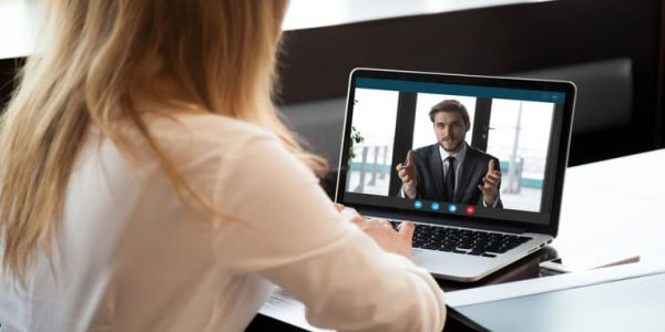 Over the shouler image of a female speaking to a colleague or business via laptop