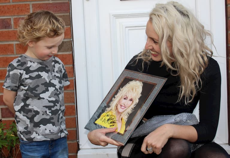 Mum and young son looking at picture of Dolly Parton