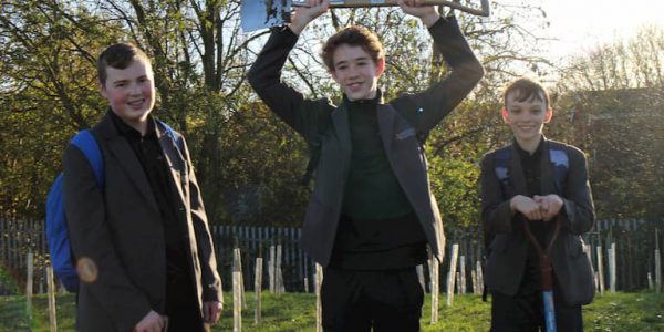 Threee young teenage boys holding spades in a field of newly planted trees