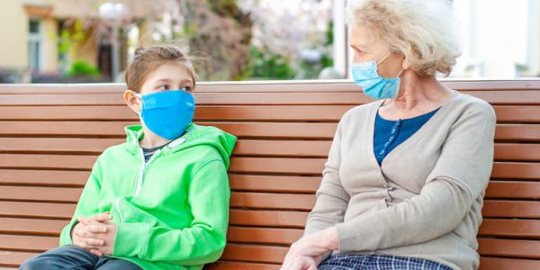 Young boy and older woman one bench wearing face masks