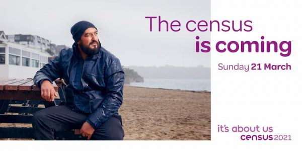 Man in warm clothing sitting on a beach and the words 'The census is coming'