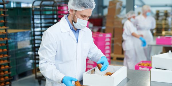 Photograph of a worker in a food factory wearing a mask