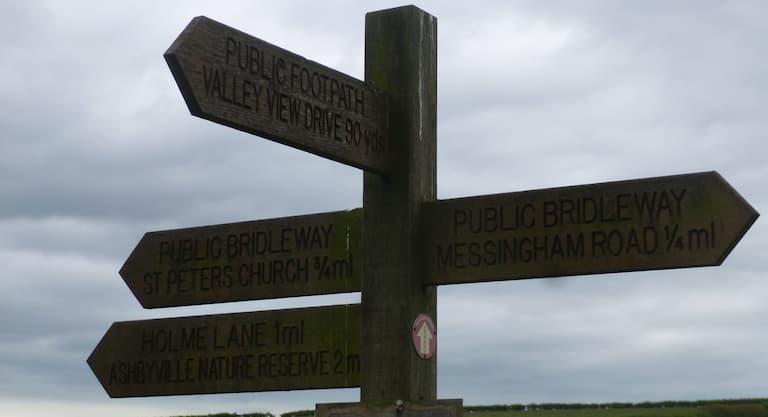 Wooden fingerpost sign at Bottesford Beck