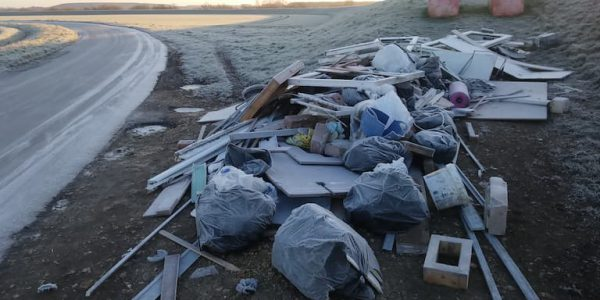 Flytipped rubbish and debris by the side of the road on a frosty day