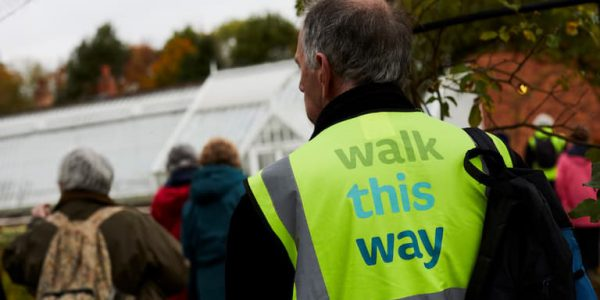 A walking group, including a man in a high vis with the words Walk This Way