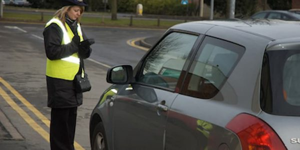 A parking warden checking a car parked on double yellow lines