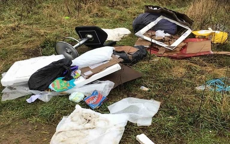 Pile of fly-tipped rubbish on grass