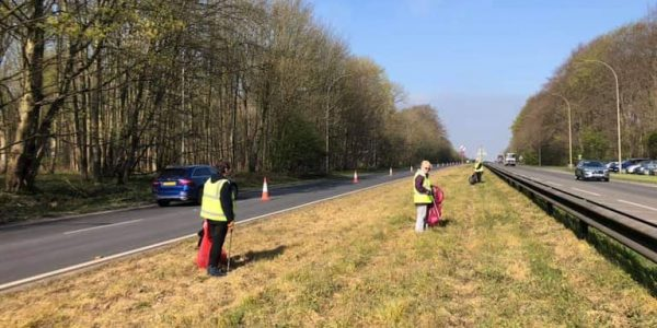 Three peopl ein high vis collecting litter from grass verge alongside a busy road