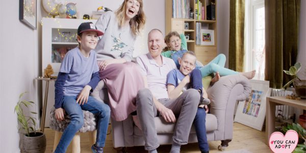 Photograph of parents and adopted children on a sofa