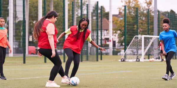Photograph of teenage girls playing football