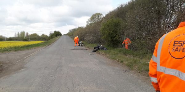 Contractors in high vis collecting rubbish on a country lane