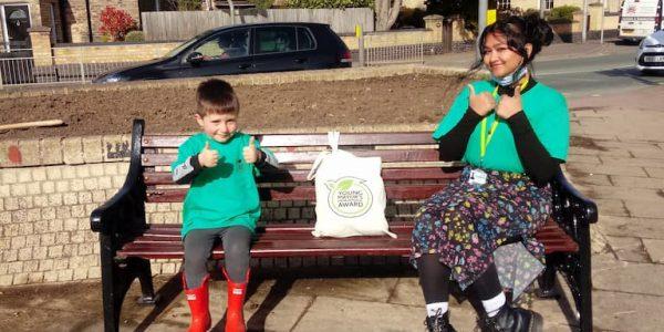 Jack Johnson and Zaynah Jamal sat on a bench in Brigg - receiving his environment award