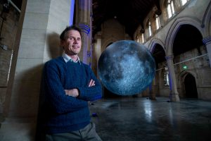 Photograph of Artist Luke Jerram pictured with The Museum of the Moon at 20-21 Visual Arts Centre