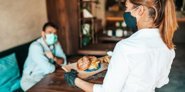 Waitress wearing a mask and gloves serving food to a man in a restaurant wearing a mask