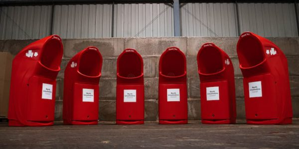 Six large red bins in a warehouse