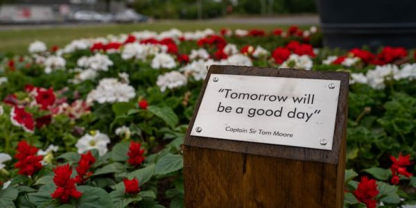 Photo of bed of red and white flowers and a plaque saying Tomorrow Is A Good Day