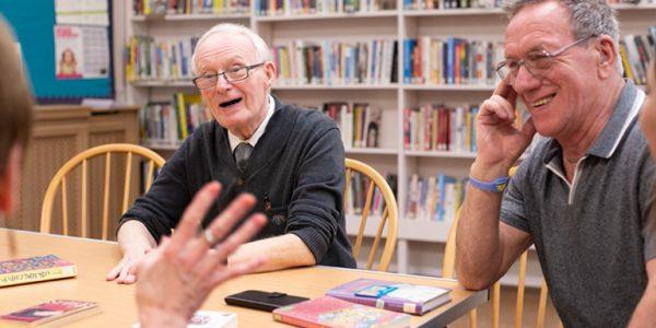 Reading Friends volunteer reads to elderly people