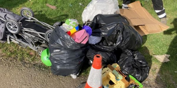 Flytipped rubbish including a pram, cardboard boxes and bin bags