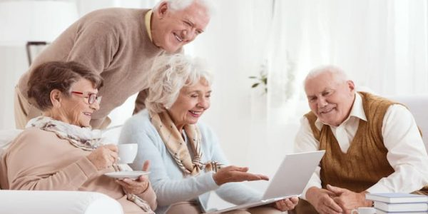 Elderly people sat in a living room using a computer