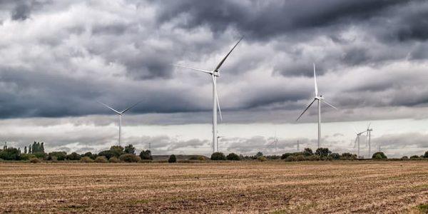 Windmills on a windfarm in farm fields in front of a cloudy sky