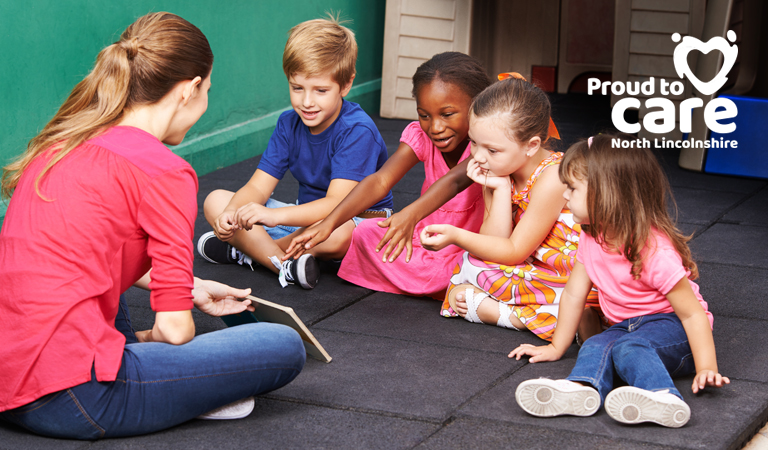 Photograph of children reading with a childminder