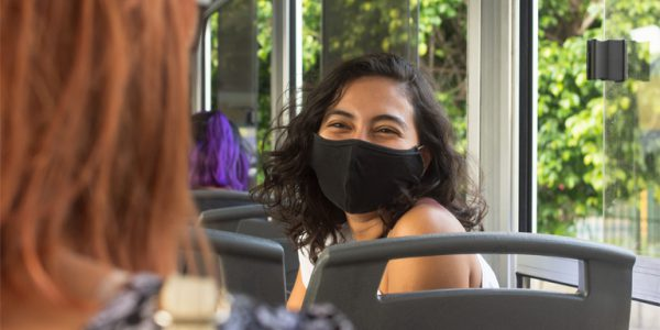 Photograph of a young woman wearing a mask on a bus