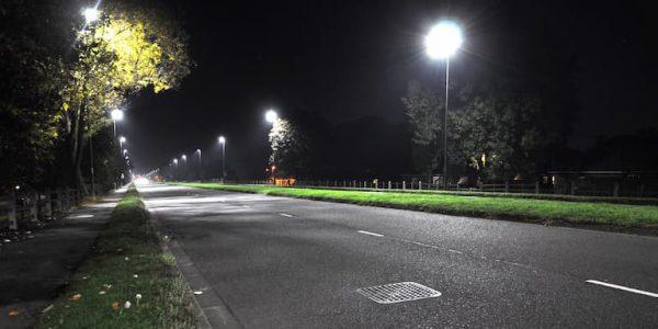 Bright LED streetlights illuminate a road at night