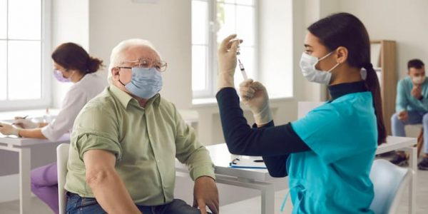 Older gentleman wearing a mask about to receive a vaccine