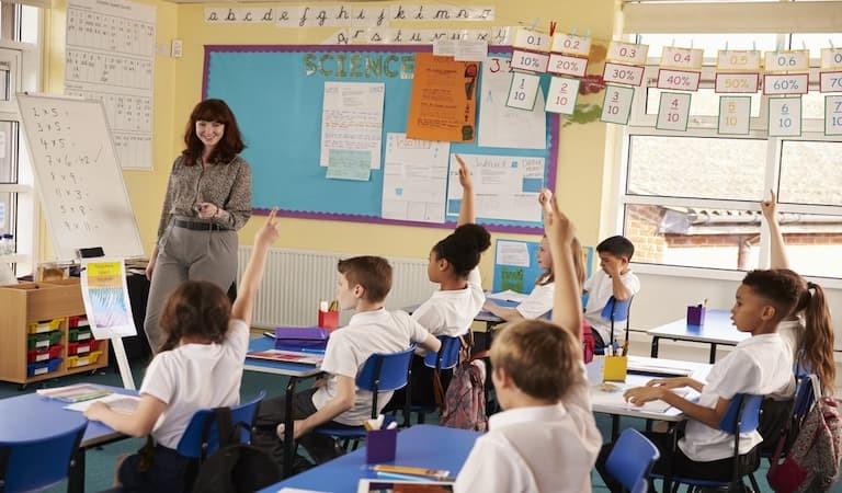 School children in class raising their hands with a teacher