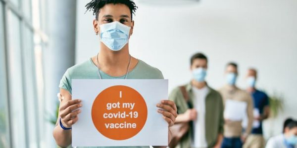 Young Male, wearing a mask and holding a 'I got my Covid-19 vaccine ' sign